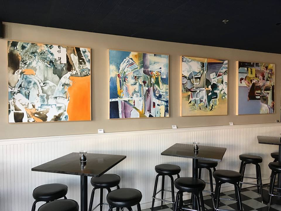 Four 40in square canvas paintings hung on a wall above tables in a restaurant